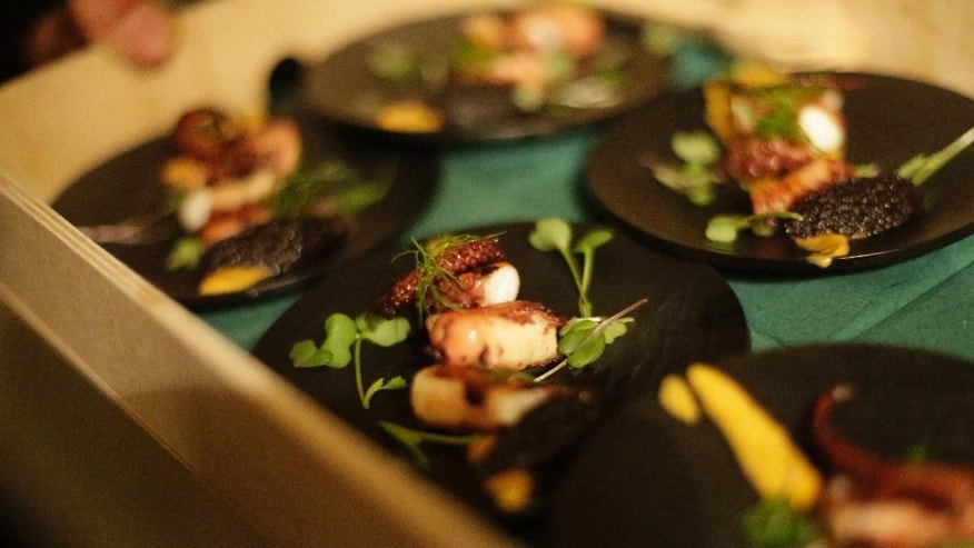 In this Monday, May 16, 2016 photo, servings of octopus prepared by Jonah Reider, is served during Brownstone, an experiential treasure-hunt of sound, taste, and color at the American Irish Historical Society, in New York. Reider, a Columbia University student who wowed food experts with sublime creations served in his spartan dorm has graduated. Reider already has thousands of fans, including Stephen Colbert and famed food critic Ruth Reichl.   (AP Photo/Frank Franklin II)