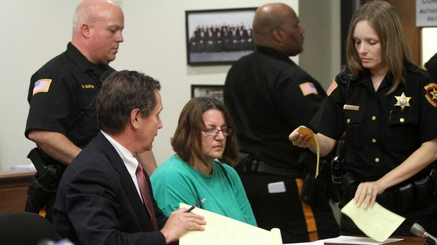 FILE - In this Sept. 16, 2014 file photo, Michelle Lodzinski, center, sits beside her attorney Gerald Krovatin during her arraignment in New Jersey Superior Court in New Brunswick, N.J. Lodzinski, a resident of Port St. Lucie, Fla., was convicted on Wednesday, May 18, 2016, of killing her 5-year-old son Timothy Wiltsey in New Jersey in May 1991. (Jason Towlen/Home News Tribune via AP, Pool, File)