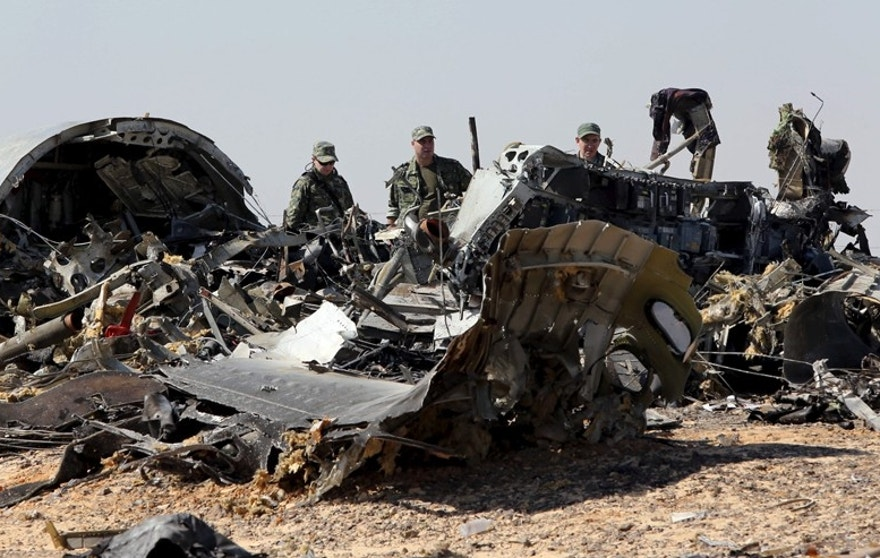 Military investigators from Russia stand near the debris of a Russian airliner at the site of its crash at the Hassana area in Arish city, north Egypt, November 1, 2015. Russia has grounded Airbus A321 jets flown by the Kogalymavia airline, Interfax news agency reported on Sunday, after one of its fleet crashed in Egypt's Sinai Peninsula, killing all 224 people on board. REUTERS/Mohamed Abd El Ghany - RTX1U8DY