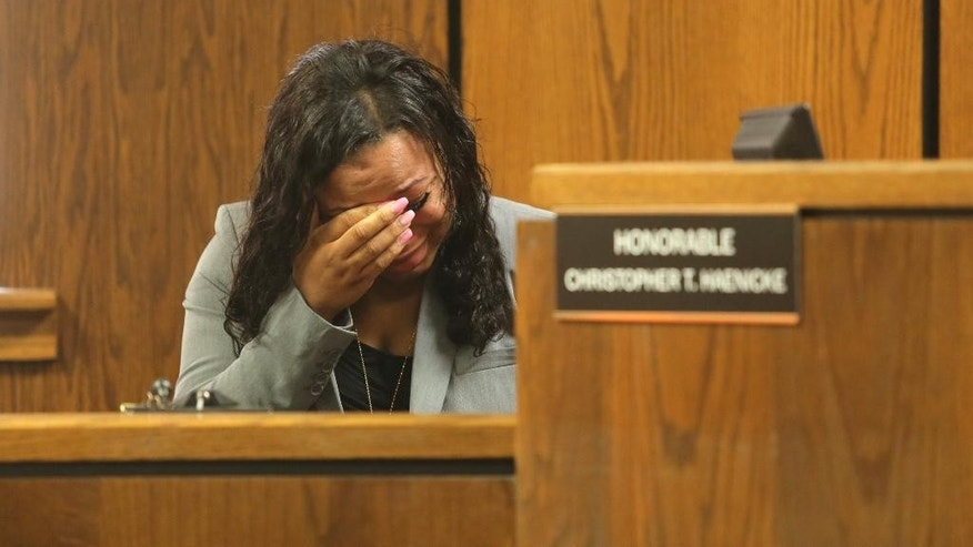 Witness and survivor Tiana Carruthers cries on the witness stand as Kalamazoo County Deputies remove defendant Jason Dalton after an outburst during his preliminary examination in district court on Friday, May 20, 2016 in Kalamazoo, Mich. Prosecutors say Dalton gunned down six people and wounded two others in the Kalamazoo area over several hours on Feb. 20 while driving for Uber that night. ( Mark Bugnaski/Kalamazoo Gazette-MLive Media Group via AP, Pool)