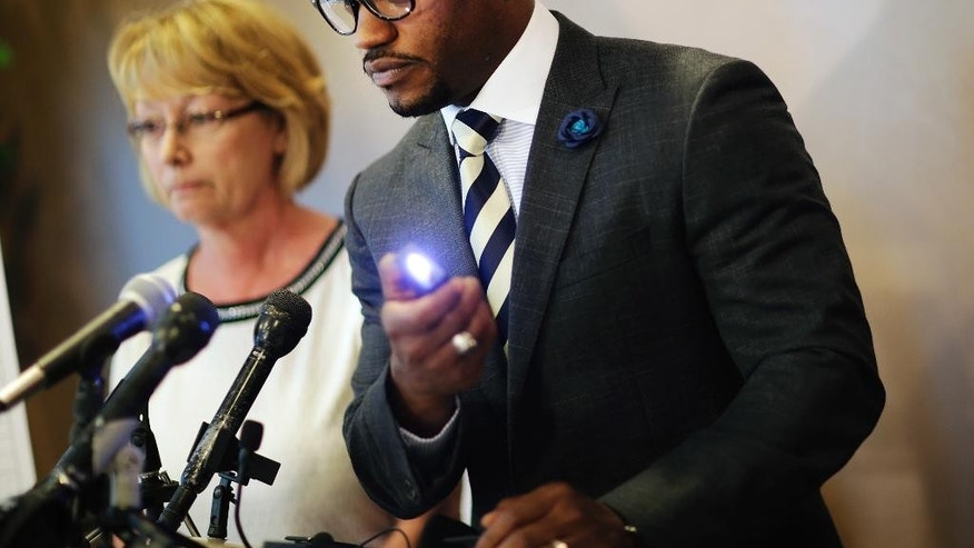 "Attorney Chris Stewart, right, demonstrates the use of a taser, while standing next to Mary Ann Sherman, during a news conference in response to a video showing her son's struggle with police officers Friday, May 20, 2016, in Atlanta. Two deputies yell ""Stop fighting!"" and ""He's got my Taser!"" as they repeatedly stun Chase Sherman, handcuffed in the back of a vehicle, commanding him to relax even as he insists ""I'm dead,"" shortly before he stops breathing, body-camera video from the incident shows. The video shows the Nov. 20 incident in the back of an SUV in Coweta County, outside Atlanta. Sherman, 32, of Destin, Florida, was pronounced dead at a hospital later that day.(AP Photo/David Goldman)"