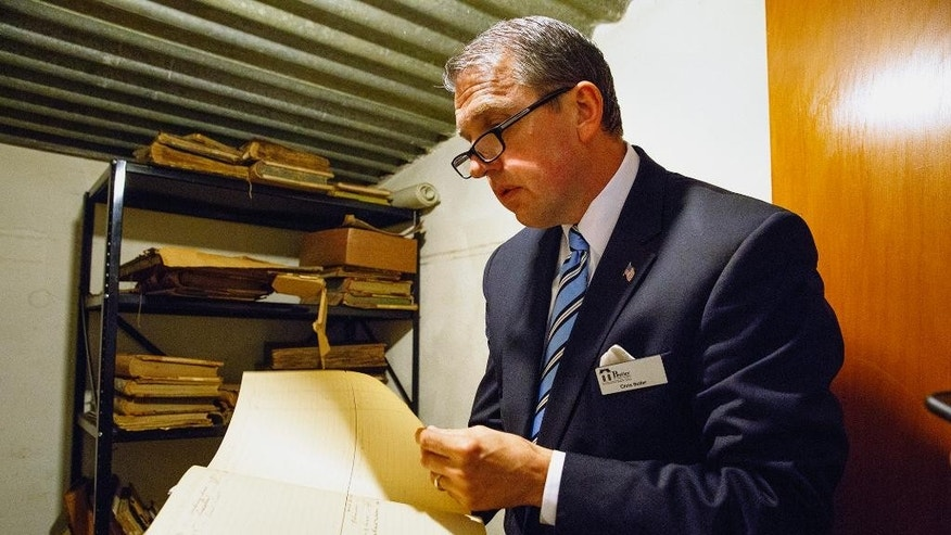In this May 18, 2016 photo, Butler Funeral Homes president Chris Butler looks through ledgers kept by the Boardman-Smith Funeral Home in Springfield, Ill. Boardman-Smith, which was founded in 1848 and acquired by Butler last year, handled the funeral arrangements for Mary Todd Lincoln. An itemized list believed to be from the former first lady's funeral has resurfaced after the two Springfield funeral homes merged. (Rich Saal/The State Journal-Register via AP) MANDATORY CREDIT