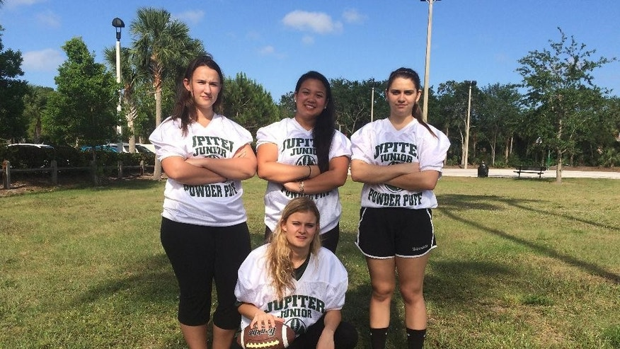FILE - In this May 2, 2016, file photo, Jupiter High School powderpuff football players, from left, Caitlin Walsh, Megan Mendoza, Haley Osborne and Savannah Tardonia (in front with ball) pose for a group photo in Jupiter, Fla. Almost sacked for safety concerns after 50 years, the nation's last tackle powderpuff football game will now be played.  Students and parents from Florida's Jupiter High School persuaded the town to sponsor the all-girl game after the principal cancelled, fearing girls would be injured. (AP Photo/Terry Spencer, File)