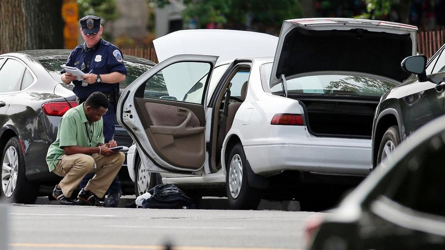 Police officials investigate a Toyota sedan on Constitution Avenue, Friday, May 20, 2016 in Washington, after a Secret Service agent shot a man with a gun who approached a checkpoint outside the White House and refused to drop his weapon, the Secret Service said. Officals searched a Toyota sedan that the gunman was believed to have driven and was parked on Constitution Avenue. The agents found ammunition inside the car, said the official, who spoke on condition of anonymity because the official was not authorized to release the information.  (AP Photo/Alex Brandon)