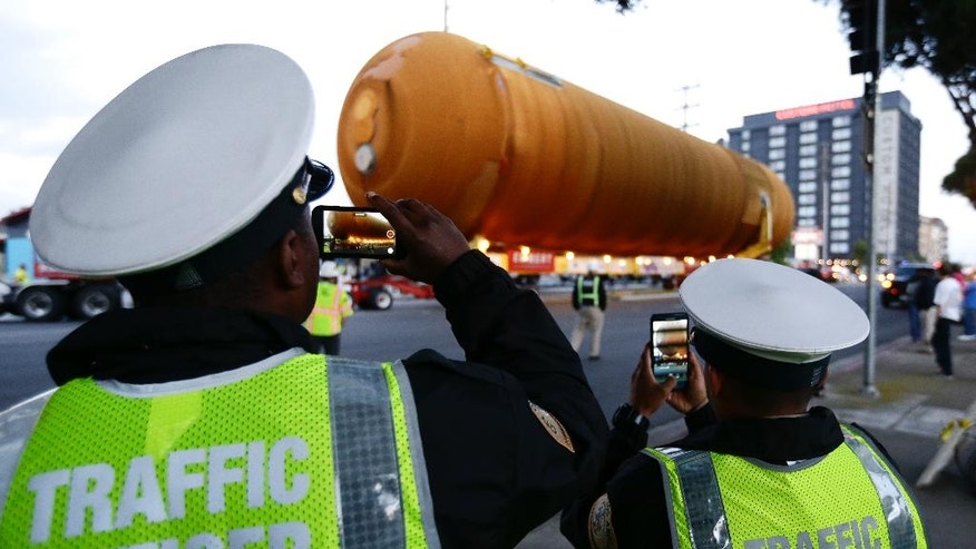 Traffic officers take photos with their phones as a space shuttle external propellant tank is moved through the streets of Los Angeles on Saturday, May 21, 2016. The ET-94 will be displayed with the retired space shuttle Endeavour at the California Science Center. (AP Photo/Chris Carlson)