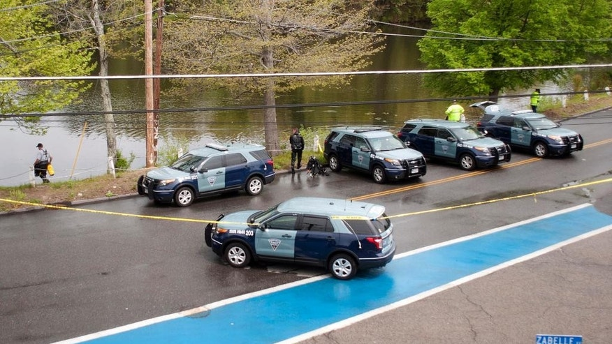 Massachusetts State Police divers search Stoneville Pond near the site where Auburn police Officer Ronald Tarentino was fatally shot during a traffic stop in Auburn, Mass., Sunday, May 22, 2016. A suspect is on the loose, authorities said. (Rick Cinclair/Worcester Telegram & Gazette via AP) MANDATORY CREDIT