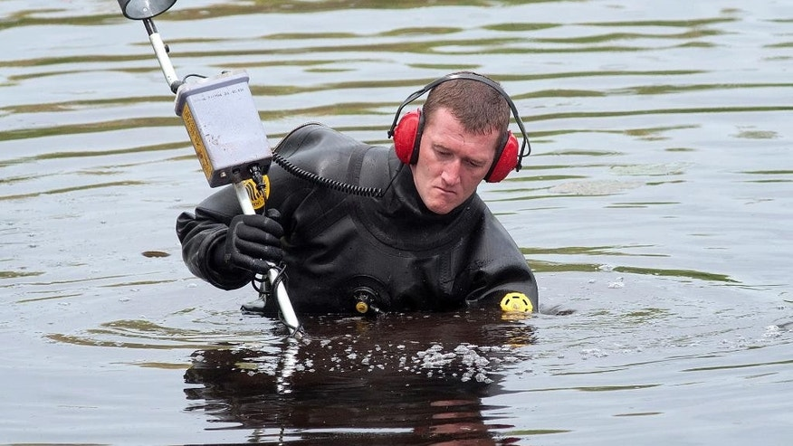 A Massachusetts State Police diver uses a metal detector to search Stoneville Pond near the site where Auburn police Officer Ronald Tarentino was fatally shot during a traffic stop in Auburn, Mass., Sunday, May 22, 2016. A suspect is on the loose, authorities said. (Rick Cinclair/Worcester Telegram & Gazette via AP) MANDATORY CREDIT