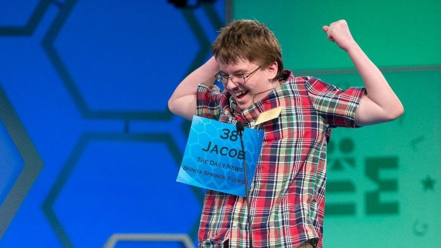 "FILE - In this May 29, 2014 file photo, Jacob Williamson of Cape Coral, Fla., reacts after correctly spelling his word ""harlequinade"", during the semifinals of the Scripps National Spelling Bee at National Harbor in Oxon Hill, Md. The Scripps National Spelling Bee has a profound influence on the lives of many young people who participate. Year after year, they keep coming back. Williamson has taken on many roles in the two years since his memorable run to the finals at the Scripps National Spelling Bee. He's been a coach to younger spellers, an official at local bees, a scout who identifies promising young talent and, at times, a vocal critic of Scripps.  (AP Photo/Manuel Balce Ceneta, File)"