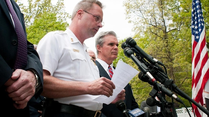 Auburn Police Chief Andrew Sluckis reads a statement about Auburn police Officer Ronald Tarentino who was was fatally shot during a traffic stop in Auburn, Mass., Sunday, May 22, 2016. Worcester County District Attorney Joseph D. Early, Jr., right, joins Sluckis at the briefing. (Rick Cinclair/Worcester Telegram & Gazette via AP) MANDATORY CREDIT