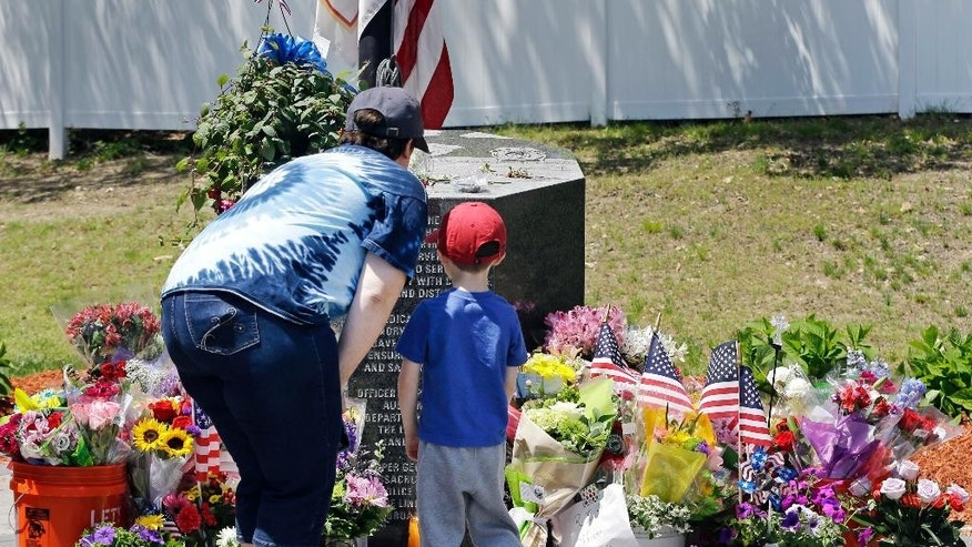 Danielle Dowd and her son Lucas pause before a memorial set up for slain Auburn police Officer Ronald Tarentino outside the police station, Monday, May 23, 2016, in Auburn, Mass. The man suspected of killing Tarentino during a weekend traffic stop had a lengthy criminal record and had been released from a maximum-security prison in 2013, officials said Monday. (AP Photo/Elise Amendola)