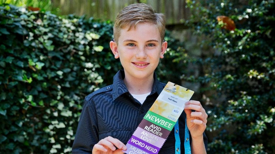 Neil Maes, 11, of Belton, S.C., holds up his National Spelling Bee badge at The Alexander Graham Bell Association for the Deaf and Hard of Hearing (AG Bell) in Washington, Tuesday, May 24, 2016. Maes was born deaf and now hears with the helps of cochlear implants. The boy will participate in his first National Spelling Bee on Wednesday, May 25, 2016 . (AP Photo/Jacquelyn Martin)