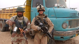 HOLD FOR USE WITH STORY MOVING FRIDAY, MAY 20, 2016-This 2007 photo provided by Chase Millsap shows Millsap with the Captain standing next to a suspected truck bomb following a successful raid in Al Anbar, Iraq. After three tours of duty in warn-torn Iraq, including one that nearly took his life, Millsap returned to the United States to earn a master's degree in public policy and get on with a civilian life. For the past two years, the former Green Beret soldier has been fighting another battle to gain political asylum for his brother in arms, a man he simply calls The Captain, a soldier who fought alongside him during two of Millsap's tours in Iraq. (Chase Millsap via AP)