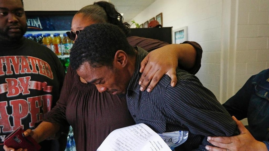 Joshua Blunt, 25, center, is escorted out of the Grenada County Jail, by family members after being released from the Grenada County Jail in Grenada, Miss., Tuesday, May 24, 2016. Blunt, who is charged with second degree murder, is accused of leaving his 8-month-old daughter in the back of his car where she later died. He was released without bail. (AP Photo/Rogelio V. Solis)