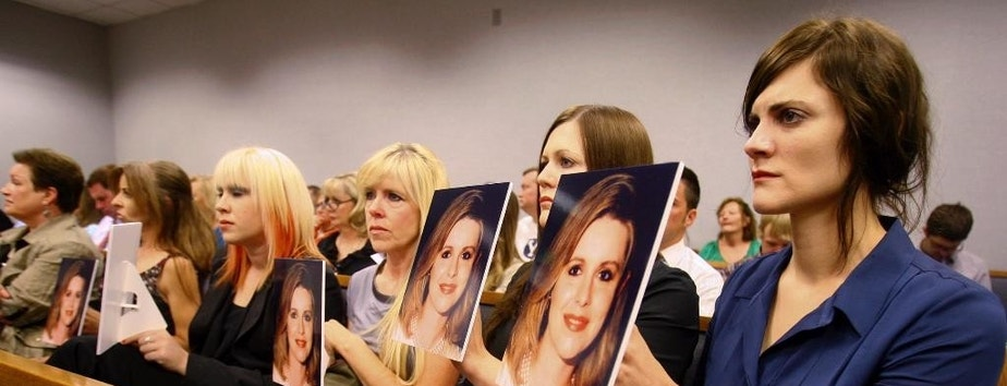 FILE - In this Aug. 27, 2012 file photo, family members hold up photos of Michele MacNeill facing Martin MacNeill as he enters the courtroom in Provo, Utah. MacNeill, who was found guilty of giving his wife drugs prescribed after cosmetic surgery and leaving her to drown in the bathtub of their home in 2007 so he could begin a new life with his mistress, will appear before a state appeals court Tuesday, May 24, 2016, in a long shot attempt to get his conviction overturned based on disputed testimony from a former cellmate. (Scott G Winterton/The Deseret News via AP, Pool, File)