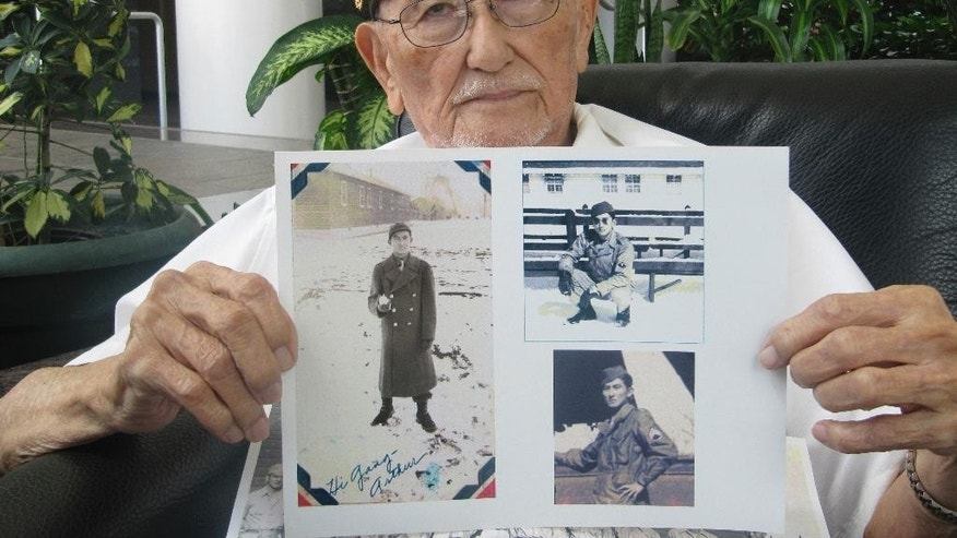 FILE - In this May 3, 2016 file photo, Arthur Ishimoto, 93, a Japanese-American and U.S. Army Military Intelligence Service veteran, poses with archival photographs of himself as he is interviewed in Honolulu. Ishimoto believes dropping the atomic bombs on Japan saved a million American lives - including his own - as well as at least 5 to 10 million Japanese lives. (AP Photo/Audrey McAvoy, File)