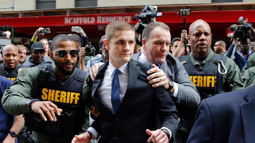 John Nero, center left, and Edward Nero, center right, brother and father of Officer Edward Nero, one of six Baltimore city police officers charged in connection to the death of Freddie Gray, are escorted out of a courthouse after Nero was acquitted of all charges in his trial in Baltimore, Monday, May 23, 2016. (AP Photo/Patrick Semansky)