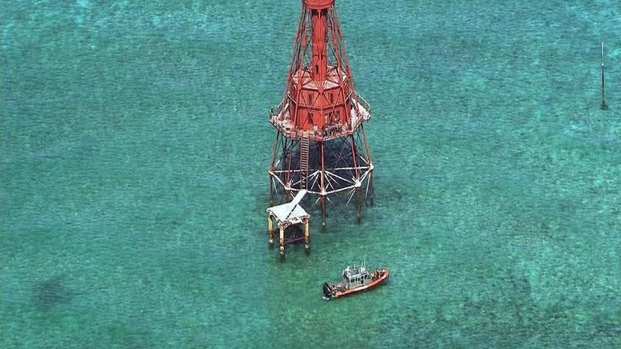 In this Friday, May 20, 2016 image made from video a group of Cubans stand atop American Shoal Lighthouse off Sugarloaf Key in a standoff with Coast Guard, in the Florida Keys. The group of migrants who fled Cuba in a homemade boat and climbed onto the 136-year-old lighthouse off the Florida Keys should be allowed to stay in the U.S., according to a federal lawsuit filed on their behalf. (WSVN-TV via AP)