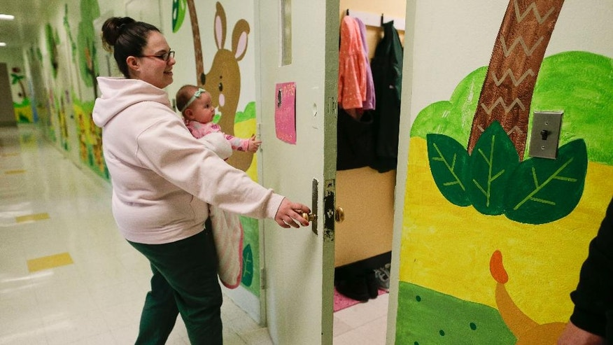 In this April 12, 2016 photo, holding her daughter, Codylynn, Jennifer Dumas opens the door to her room inside the nursery at the Bedford Hills Correctional Facility, in Bedford Hills, N.Y. Bedford Hills has one of only eight working prison nurseries where women live with their babies, out of more than 100 women's prisons around the country. (AP Photo/Julie Jacobson)