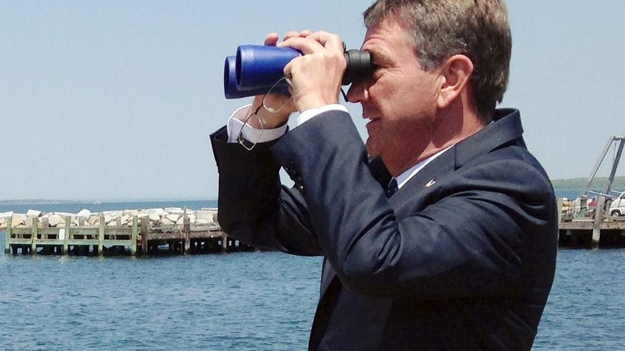 U.S. Defense Secretary Ashton Carter watches an unmanned surface vehicle navigate a course in the bay which he had plotted on a computer at the Naval Undersea Warfare Center Wednesday, May 25, 2016, in Newport, R.I. Carter told students at the nearby U.S. Naval War College in Newport that the government needs to develop technology faster and reconnect with the tech industry. (AP Photo/Jennifer McDermott)