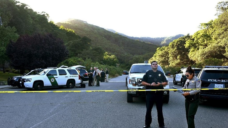 In this photo taken Wednesday, May 25, 2016, Marin County Sheriff and Novato police members gather at a command post to form a manhunt following at attack on two students in Novato, Calif. Attackers shot two students near a San Francisco Bay Area high school, killing one and sending another to a hospital in an incident that prompted the closing of the campus, authorities said Thursday. Both victims were students at Novato High School. (Robert Tong/Marin Independent Journal via AP)