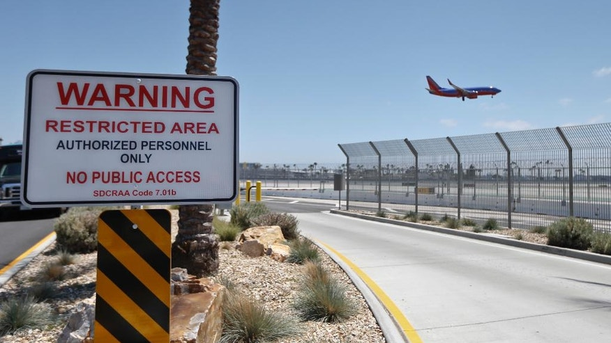 In this Friday, May 13, 2016, photo, a commercial airliner lands at San Diego International Airport, where multiple layers of fencing topped with razor wire protects the airport grounds. An Associated Press investigation has documented perimeter breaches at many of the busiest airports in the U.S. (AP Photo/Lenny Ignelzi)