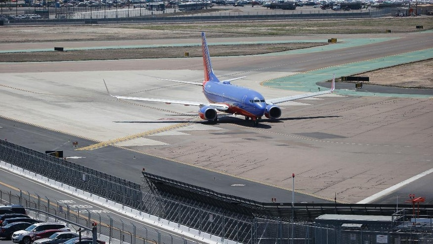 In this Friday, May 13, 2016, photo, as a commercial airliner taxis for takeoff, the perimeter fencing and razor wires show the layers of security at San Diego International Airport. An Associated Press investigation has documented perimeter breaches at many of the busiest airports in the U.S. (AP Photo/Lenny Ignelzi)