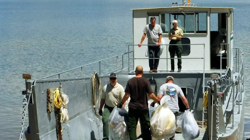 This Tuesday, May 24, 2016 photo provided by the U.S. Forest Service shows workers loading bags of trash on a boat after cleaning up a half-mile-wide swath of trash left behind by about 1,000 campers after an annual trip to Lake Shasta, Calif., by fraternity and sorority members