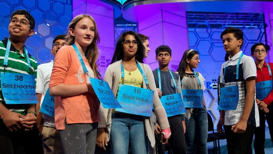 The final spellers who made it into the evening televised final round gather around on stage after the completion of the morning of competition of the 2016 National Spelling Bee, in National Harbor, Md., Thursday, May 26, 2016. From left are, Sreeniketh A. Vogoti, 13, of Florida; Rutvik M. Gandhasri, 12, of California; Sylvie Lamontagne, 13, of Colorado; Snehaa Ganesh Kumar, 16, of Calif.; Mitchell A. Robson, 14, of Massachusetts; Nihar Saireddy Janga, 11, of Texas; Smrithi Upadhyayula, 13, of Texas; Jairam Jagadeesh Hathwar, 13, of New York.  (AP Photo/Jacquelyn Martin)