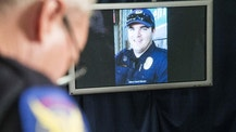 The image of Phoenix police officer David Glasser is displayed during a news conference as Phoenix Police PIO Vince Lewis, left, holds his head down on Thursday May 19, 2016 in Phoenix.  Glasser died Thursday, a day after being wounded during a shooting that left a burglary suspect dead. (Nick Oza/The Arizona Republic via AP)  MARICOPA COUNTY OUT; MAGS OUT; NO SALES; MANDATORY CREDIT
