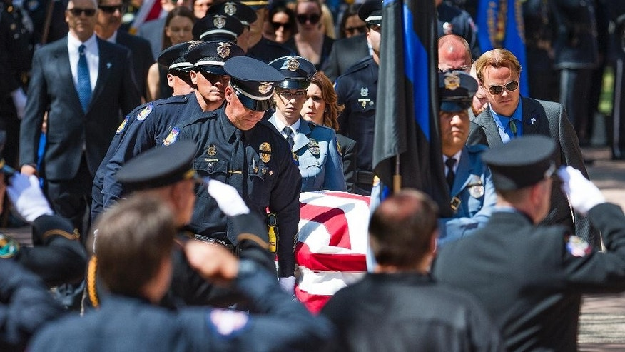 The casket of Phoenix Police Officer David Glasser is taken into Christ's Church of the Valley in Peoria Thursday, May 26, 2016, for his funeral service. Glasser died May 19, a day after he was wounded when shot by a burglary suspect who then was fatally shot by police. (Tom Tingle/The Arizona Republic via AP)  MARICOPA COUNTY OUT; MAGS OUT; NO SALES; MANDATORY CREDIT