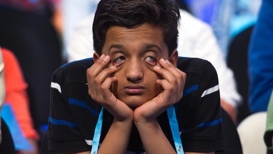 Jairam Jagadeesh Hathwar, 13, from Corning, N.Y., having already spelled his word, waits for the other spellers during the preliminary round three of the Scripps National Spelling Bee in National Harbor, Md., Wednesday, May 25, 2016. (AP Photo/Cliff Owen)