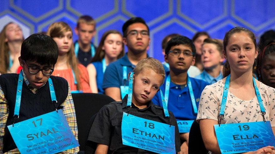 Ethan Gomulka, 11, of San Bernardino, Calif., center, puts his lanyard over his ears as competition continues in the preliminaries of the 2016 National Spelling Bee, in National Harbor, Md., Wednesday, May 25, 2016. At left is Syaal Sharifzad, 12, of Monterey, Calif., and Ella Peters, 13, of San Diego, Calif., is at right. (AP Photo/Jacquelyn Martin)