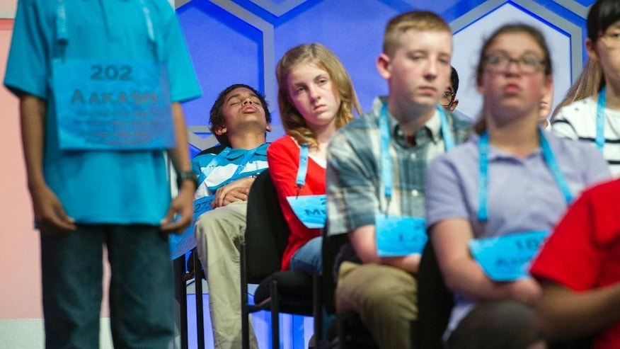 Nathan Mitchell Jarrett, 13, from La Crosse, Wis., back left, closes his eyes while waiting onstage to spell his word during the preliminary round three of the Scripps National Spelling Bee in National Harbor, Md., Wednesday, May 25, 2016. (AP Photo/Cliff Owen)