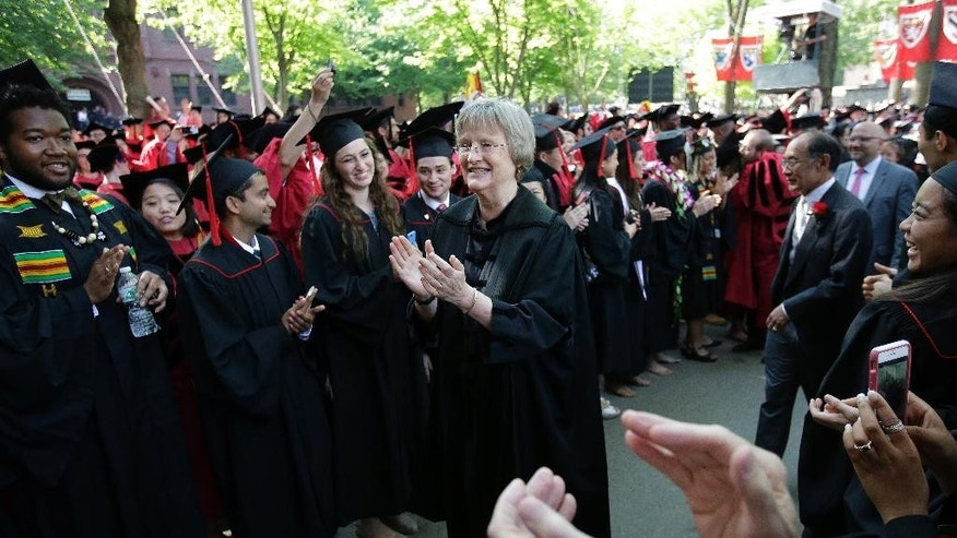 Harvard President Drew Faust, center, receives applause while proceeding toward the podium at the start of Harvard University commencement exercises, Thursday, May 26, 2016, in Cambridge, Mass. (AP Photo/Steven Senne)