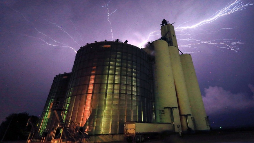 May 25, 2016: Lightning from a severe storm fills the sky behind a grain elevator in Belvue, Kan. The storm produced tornadoes near Chapman, Kan.