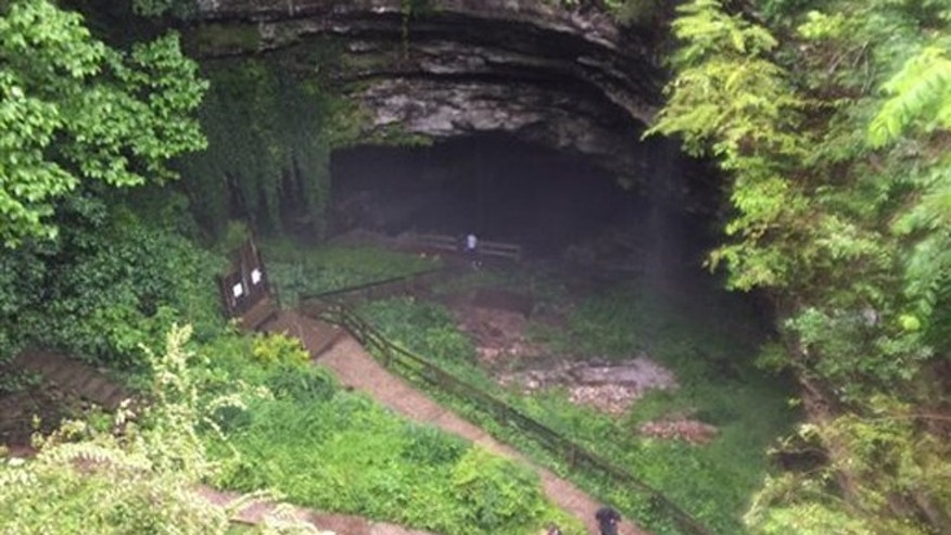 People exit Hidden River Cave after officials said over a dozen people who exploring the cave were trapped by rising water Thursday, May 26, 2016, in Horse Cave, Ky.
