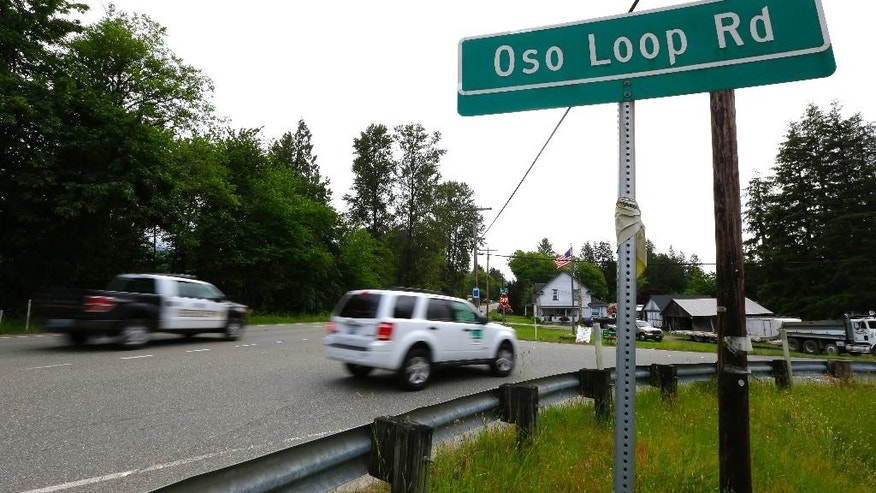 In this Wednesday, May 25, 2016 photo, cars pass Oso Loop Road near the site of a massive 2014 mudslide that killed 43 people in Oso, Wash. Patrick Shunn and Monique Patenaude, who have been missing since mid-April, lived in a house that bordered the slide, and authorities have charged the couple's neighbor John Reed, who remains at large, and his brother Tony Reed, who has surrendered to authorities, with first-degree murder in their deaths. (AP Photo/Ted S. Warren)
