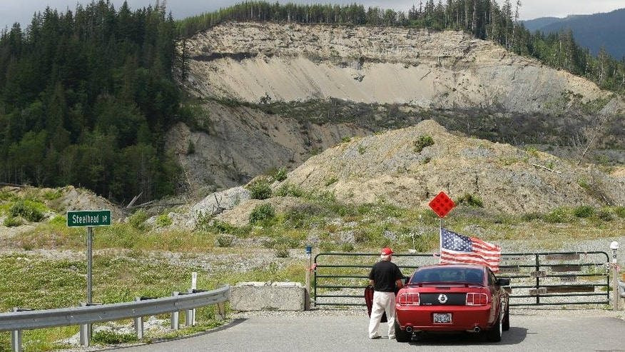 In this Wednesday, May 25, 2016 photo, a motorist pauses near a U.S. flag that had been placed near the site of a massive 2014 mudslide that killed 43 people in Oso, Wash. Patrick Shunn and Monique Patenaude, who have been missing since mid-April, lived in a house that bordered the slide, and authorities have charged the couple's neighbor John Reed, who remains at large, and his brother Tony Reed, who has surrendered to authorities, with first-degree murder in their deaths. (AP Photo/Ted S. Warren)