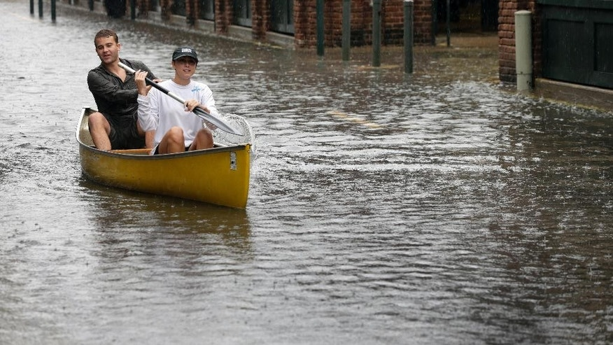 FILE- In this Oct. 3, 2015 file photo, Dillon Christ, front, and Kyle Barnell paddle their canoe down a flooded street in Charleston, S.C. The U.S. government is set to release its forecast for how many hurricanes and tropical storms are expected to form over Atlantic and Caribbean waters in the next six months. It's an annual reminder from the National Oceanic and Atmospheric Administration that coastal living comes with significant risks. (AP Photo/Chuck Burton, File)
