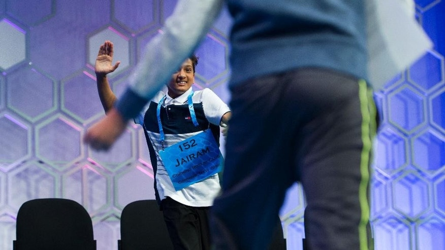 Jairam Jagadeesh Hathwar, 13, of Painted Post, N.Y., runs to high-five Nihar Saireddy Janga, 11, of Austin, Texas, foreground, after they were named the co-champions of the 2016 Scripps National Spelling Bee in National Harbor, Md., Thursday, May 26, 2016. (AP Photo/Cliff Owen)