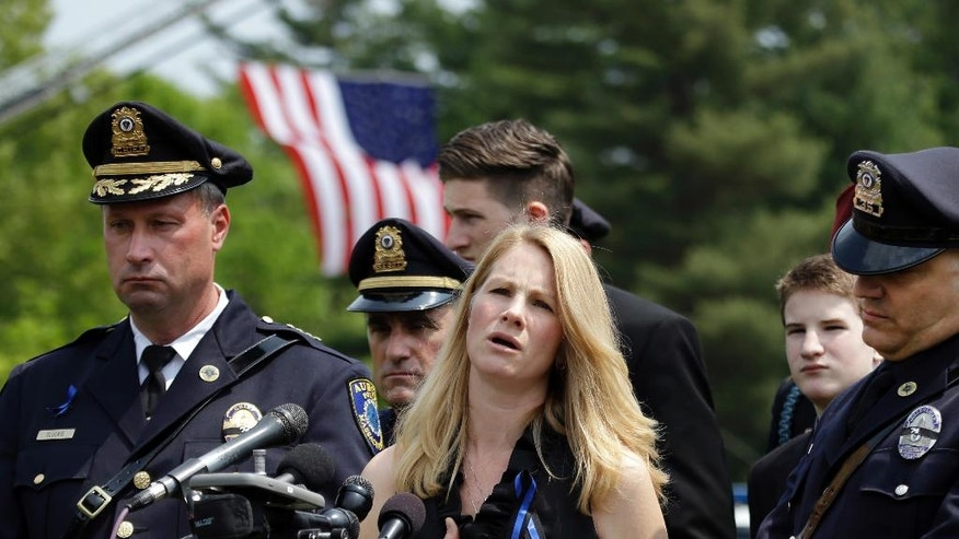 Tricia Tarentino, widow of slain Auburn Police Officer Ronald Tarentino Jr., touches her heart as she makes a statement to news media, Friday, May 27, 2016, at his funeral in Charlton, Mass. Authorities said the Massachusetts police officer was shot dead during a weekend traffic stop. At left is Auburn Police Chief Andrew Sluckis. (AP Photo/Elise Amendola)