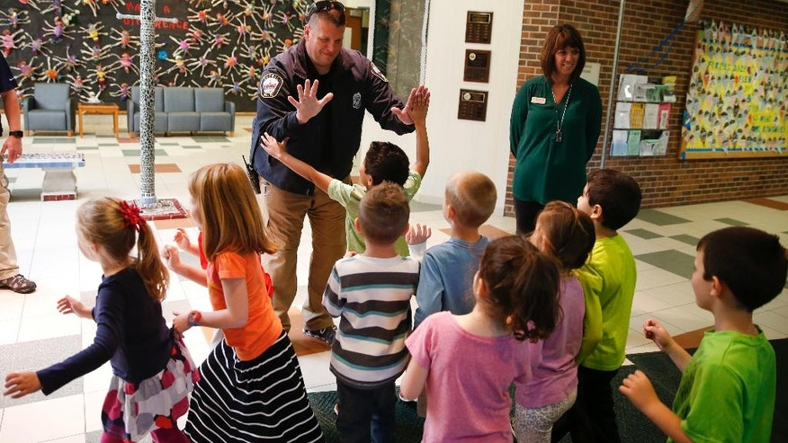 In this May 6, 2016, photo, Forest Dale Elementary School principal Deanna Pitman, right, and Carmel, (Ind.) police officer Greg DeWald welcome students as they return to the school following an intruder drill at the school in Carmel, Ind. More and more, schools these days are conducting active-shooter drills. A government report found that more than two-thirds of the school districts surveyed conduct active shooter exercises.  (AP Photo/Michael Conroy)