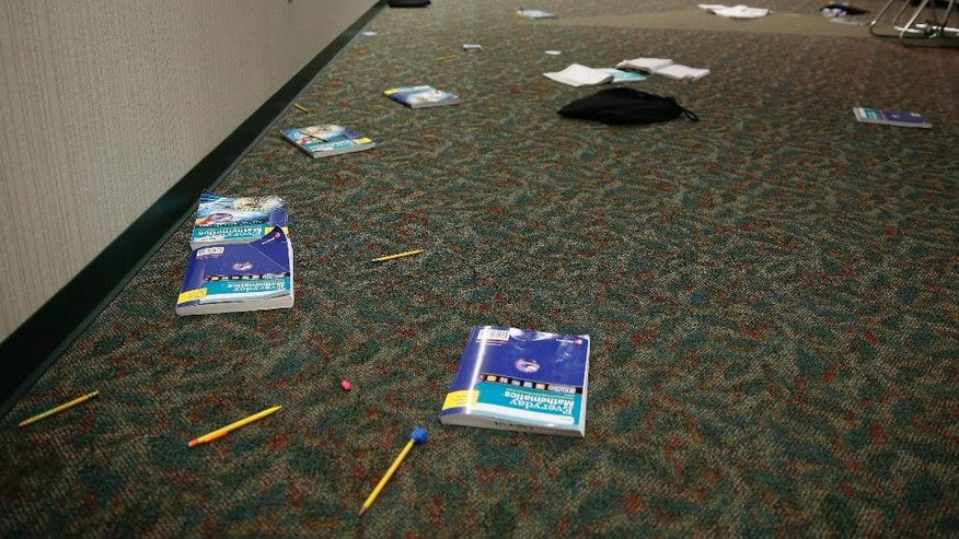 In this May 6, 2016, photo, books and supplies litter the floor as a class evacuated the area during an intruder drill Forest Dale Elementary School in Carmel, Ind. More and more, schools these days are conducting active-shooter drills. A government report found that more than two-thirds of the school districts surveyed conduct active shooter exercises. (AP Photo/Michael Conroy)