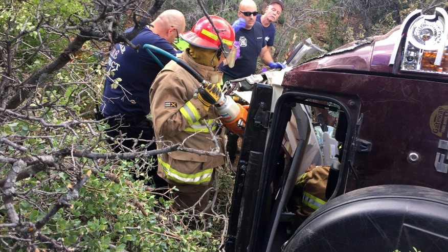 May 27, 2016: This photo provided by Kim Moore shows firefighters working to extricate a 50-year-old man from his crashed car on Mingus Mountain in Yavapai County, Arizona.
