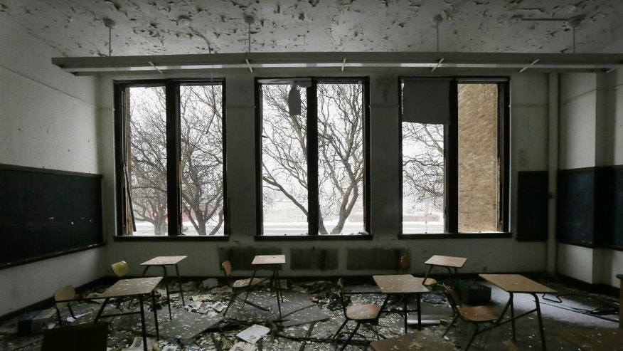 FILE- This Jan. 6, 2015, file photo, shows a vacant classroom at Southwestern High School in Detroit. The number of students enrolled in Detroit Public Schools has dropped dramatically since the 1990s, fueled by the flight of a quarter million city residents, abysmal graduation rates, financial mismanagement, and corruption. In 2002, there were 156,000 students enrolled in the district. This year, there were 46,000, a 70 percent decline. (AP Photo/Carlos Osorio, File)