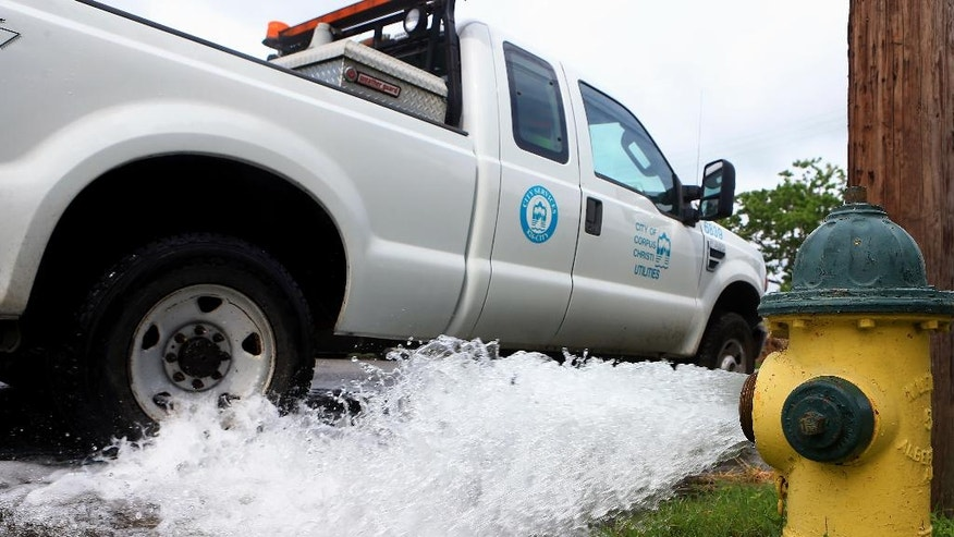 FILE - In a May 14, 2016 file photo, water is flushed out from a hydrant, on the corner of Glenmore St. and Kentner St. in Corpus Christi, Texas. The Texas Gulf Coast city has issued three orders in less than a year telling residents to boil their water to ensure it's safe to consume, including a two-week order this month that sparked outrage, contributed to the city manager's resignation and renewed questions about how to fix the problem.  (Gabe Hernandez/Corpus Christi Caller-Times via AP, File)