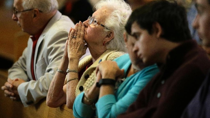 Parishioner Joanmarie Gorman, of Scituate, Mass., center, places her hands together during a planned final service at St. Frances X. Cabrini Church, Sunday, May 29, 2016, in Scituate. For more than 11 years, a core group of about 100 die-hard parishioners at the church have kept their parish open by maintaining an around-the-clock vigil in protest of a decision by the Roman Catholic Archdiocese of Boston to close it following the clergy sex abuse crisis. (AP Photo/Steven Senne)