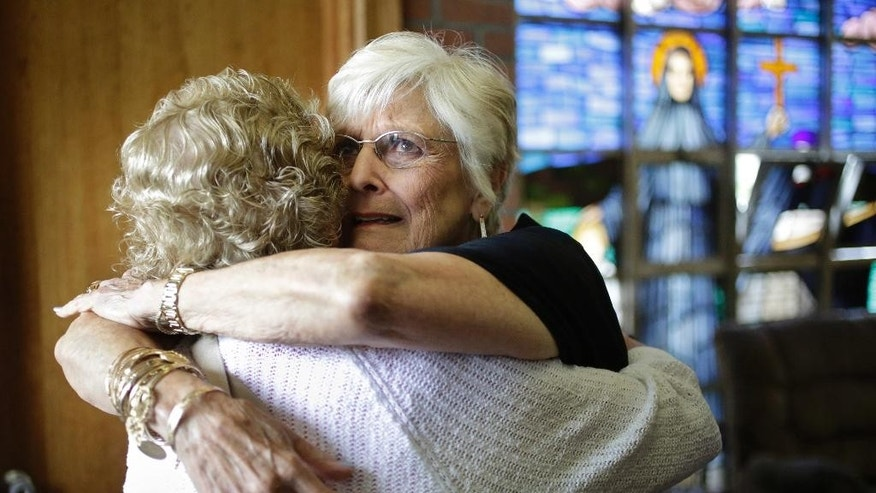 Nancy Shilts, of Scitutate, Mass., right, hugs a fellow parishioner before a planned final service at St. Frances X. Cabrini Church, Sunday, May 29, 2016, in Scituate. For more than 11 years, a core group of about 100 die-hard parishioners at the church have kept their parish open by maintaining an around-the-clock vigil in protest of a decision by the Roman Catholic Archdiocese of Boston to close it following the clergy sex abuse crisis. (AP Photo/Steven Senne)