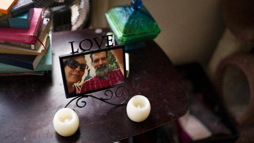In this Thursday, May 19, 2016 photo, a framed photo of Mandy Pifer and her boyfriend, Shannon Johnson, is placed next to her bed in Los Angeles. Nearly six months ago, Johnson was one of the 14 people killed in the San Bernardino terrorist attack. Pifer was a couples therapist who also volunteered with the mayor's crisis response team, but hadn't returned since the mass shooting. Now she is returning to her work, intent on paying forward the support she's received. (AP Photo/Jae C. Hong)