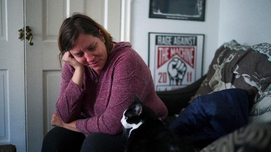In this Sunday, May 22, 2016 photo, Mandy Pifer looks at her cat while resting in her apartment in Los Angeles. Nearly six months ago, Pifer's boyfriend Shannon Johnson was one of 14 people killed in the San Bernardino terrorist attack. As a responder with the Los Angeles mayor's crisis response team, Pifer has spent the last six years comforting others in the aftermath of tragedy. But after the attack, Pifer found herself dealing with a crushing, overwhelming sadness. (AP Photo/Jae C. Hong)
